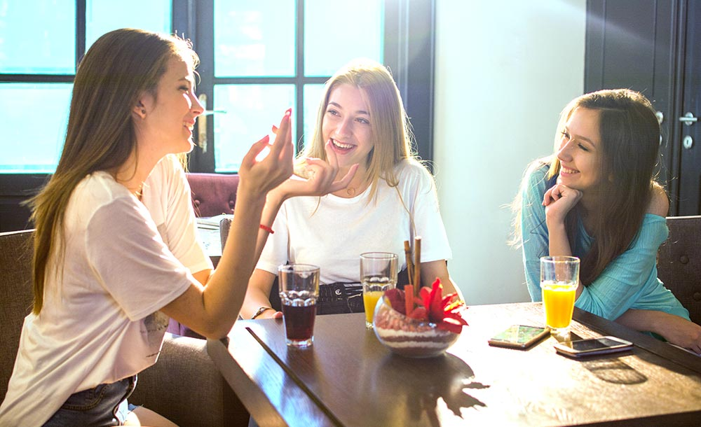 Three friends sit at a table laughing. They are happy they started online therapy for college students in Alabama with Empower Counseling.