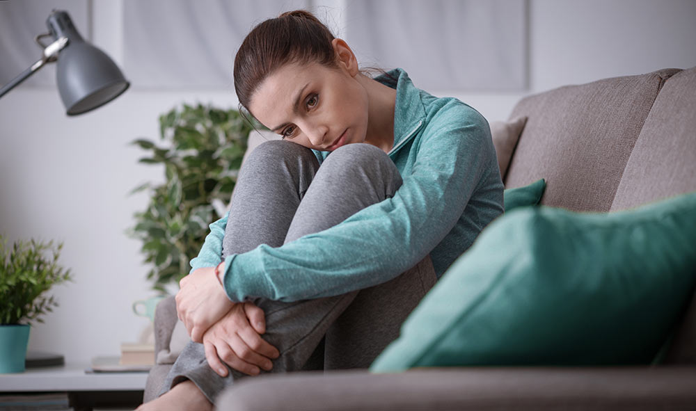 A woman looks sad, looking away from the camera. She regrets not starting anxiety counseling with an anxiety therapist in Birmingham, AL at Empower Counseling soon. n