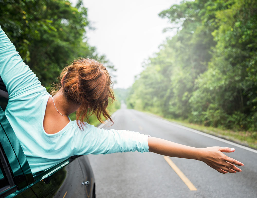 A woman puts her upper body out of the passenger window with her arms extended. She is feeling free after beginning anxiety counseling with an anxiety therapist in Birmingham, AL.