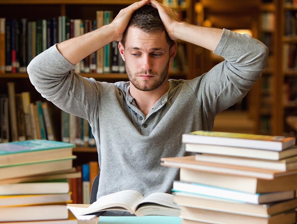 A male college student sits in a library looking overwhelmed. He is considering beginning counseling for college students in Alabama with Empower Counseling.