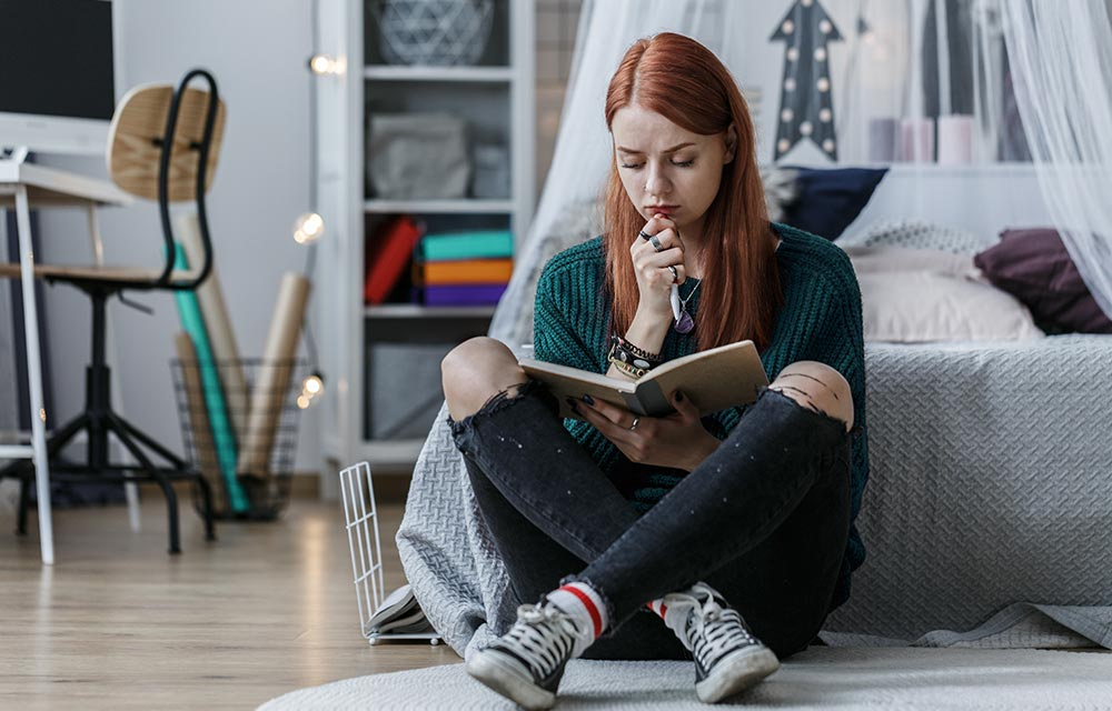 A female college students sits on her dorm floor looking stressed. She has decided it's time to begin counseling for college students in Birmingham, AL with Empower Counseling.