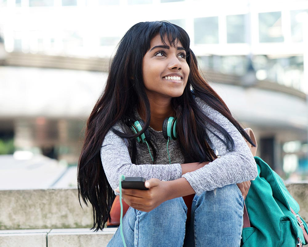 A female college student is sitting on the ground smiling. She is feeling much happier after beginning counseling for college students in Birmingham, AL with Empower Counseling.
