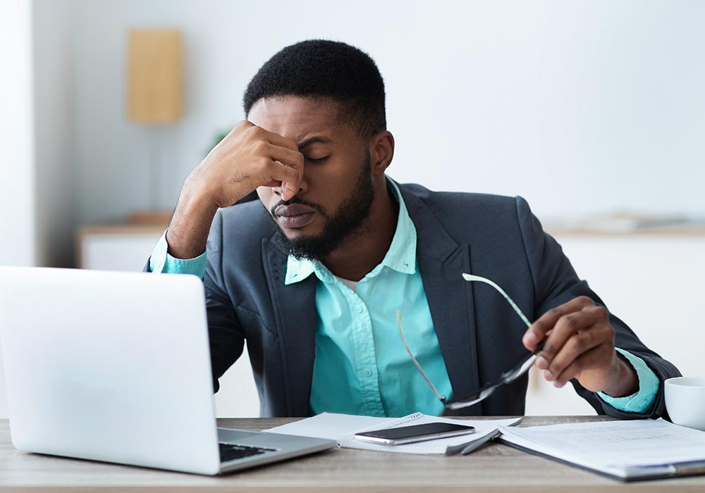 A man sits with his eyes closed and appears to be stressed. He is considering starting counseling for professionals in Birmingham, AL with Empower Counseling.