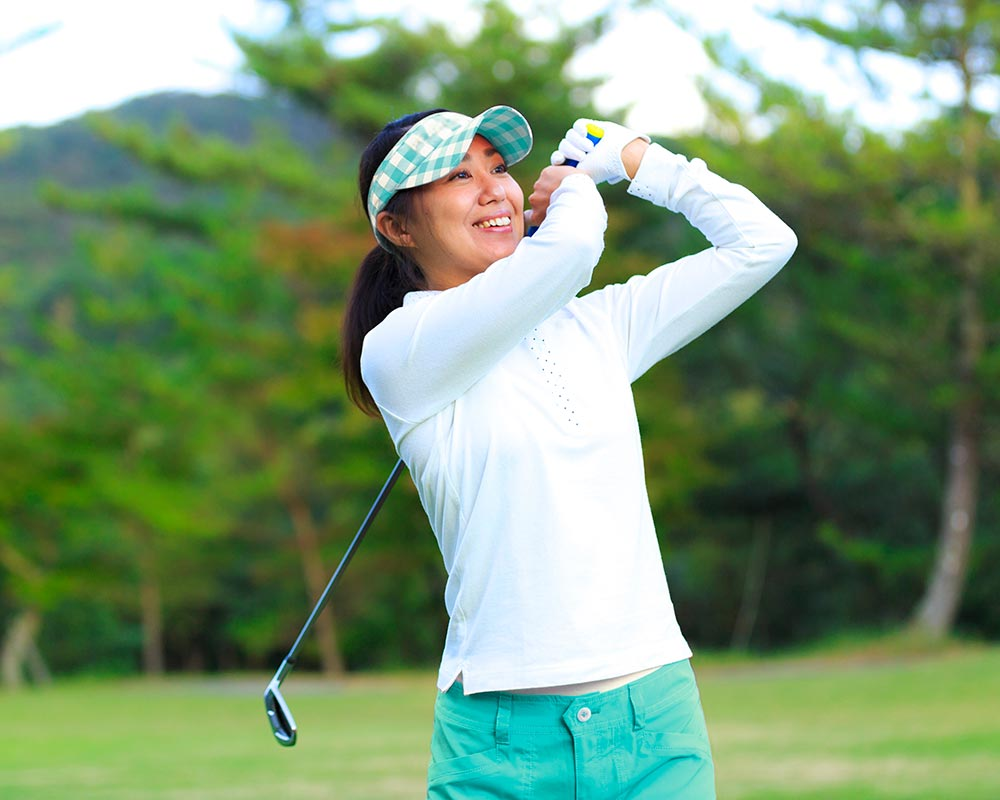 A woman smiles while playing golf. She feels rejuvenated after starting counseling for professionals in Birmingham, AL with Empower Counseling.