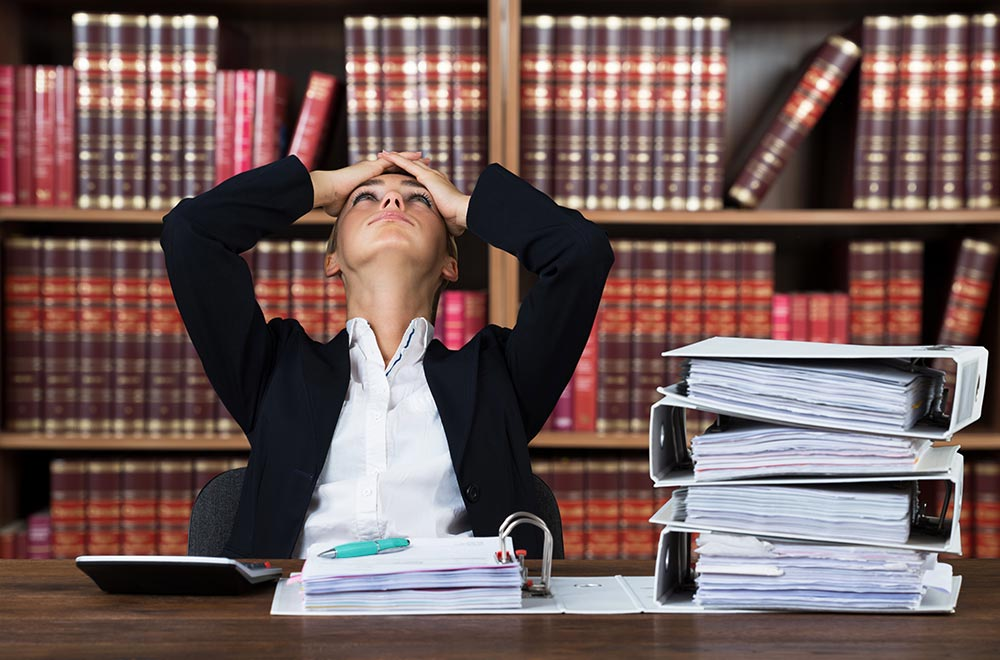 A woman sitting in a library is looking stressed. She is suffering from burnout and  has decided to pursue counseling for professionals in Birmingham, AL with Empower Counseling.
