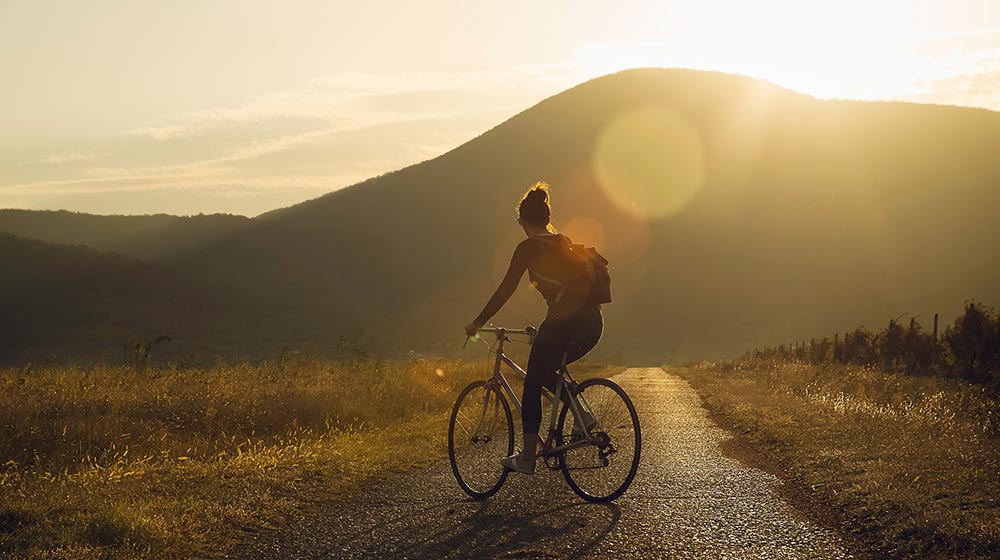 A woman cycles through the countryside. She is feeling much happier after beginning counseling for life transitions in Birmingham,AL 35532 with Empower Counseling.
