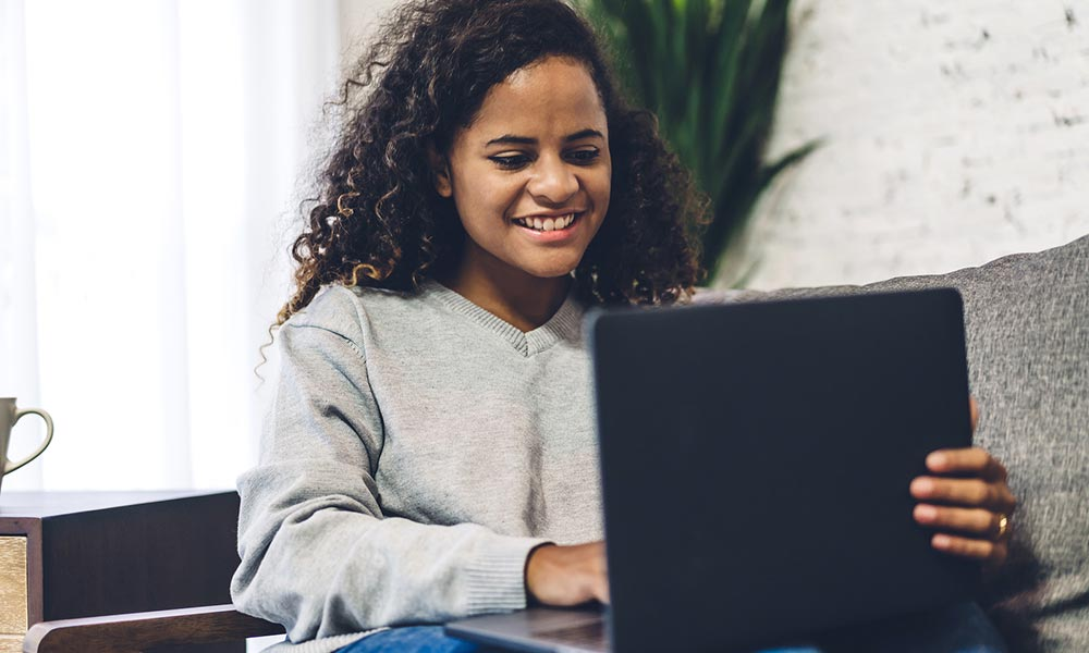 A young woman smiles while looking at her laptop. She is satisfied with her choice to start counseling for life transitions with Empower Counseling in Birmingham, AL 35532