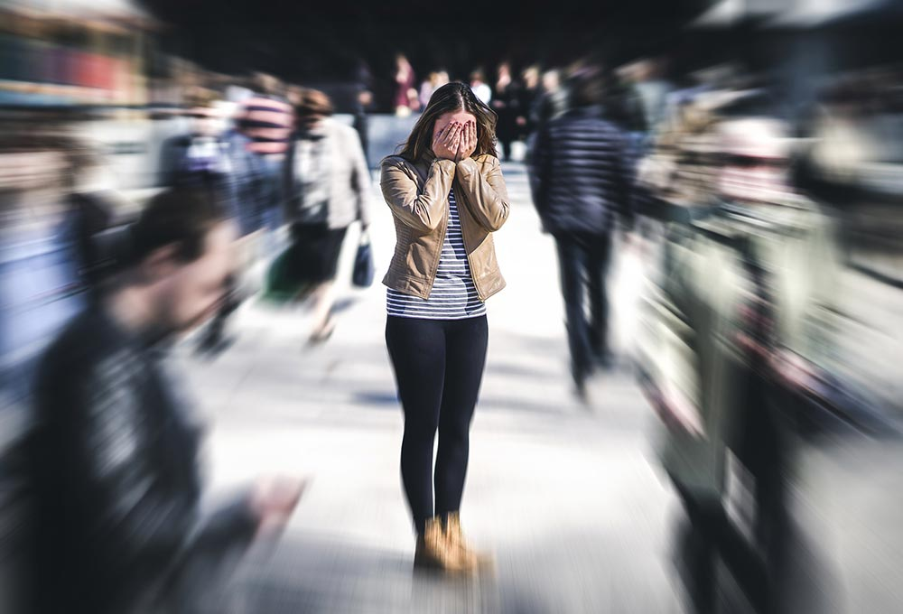 A woman stands in a crowd having a panic attack. She has decided it's time to start counseling for life transitions in Birmingham, AL 35532 with a counselor at Empower Counseling.