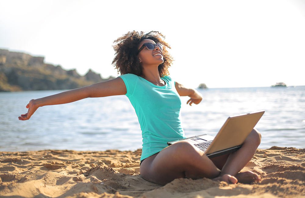 A young woman sits on a beach smiling with her arms extended, feeling empowered. She is very happy she started online therapy in Alabama with Empower Counseling.