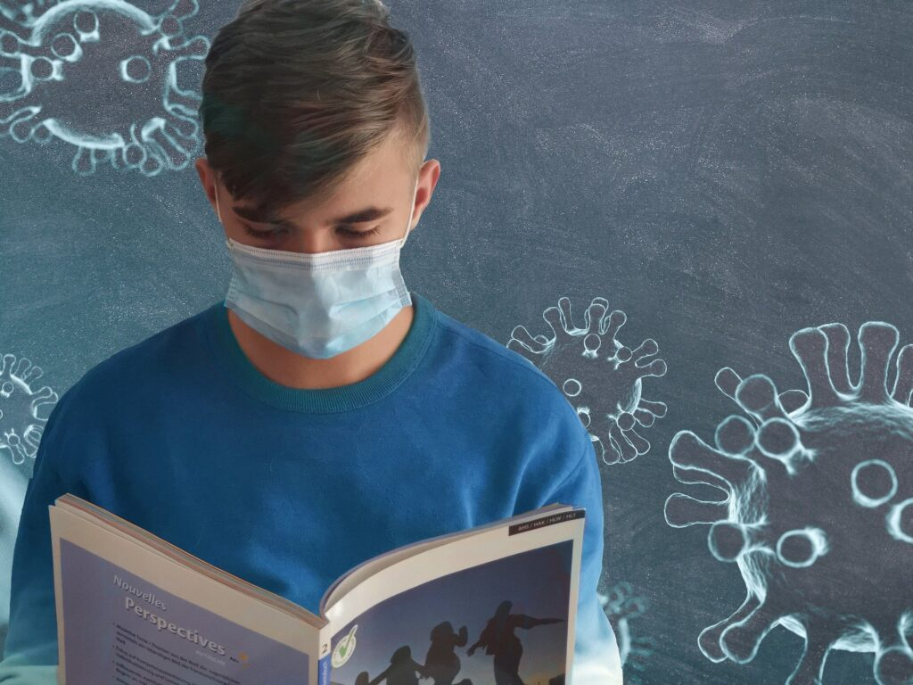 A boy wears a mask while reading a book. He has decided to  start counseling for college students in Alabama with Empower Counseling.