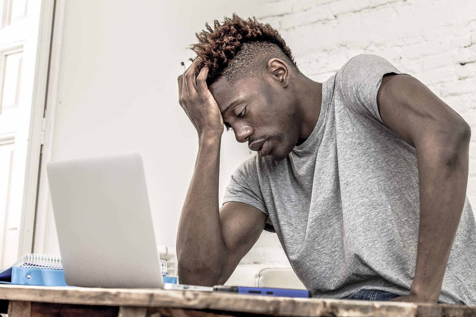 A young man at University of Alabama sits at a table looking stressed. He has decided it's time to start online therapy for college students in Alabama with Empower Counseling. Despite being located in Birmingham, AL, his online therapist is able to see him in Tuscaloosa, AL 35401L.