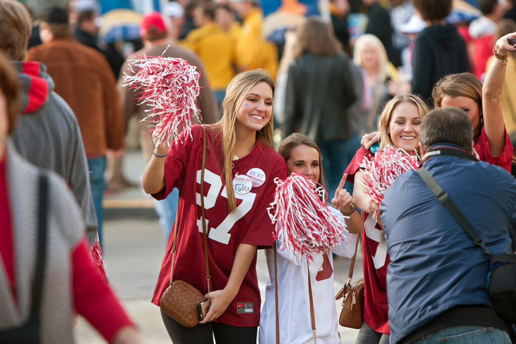 College football fans stand together to take a photo. They are feeling much happier after starting online therapy for college students in Alabama with Empower Counseling.