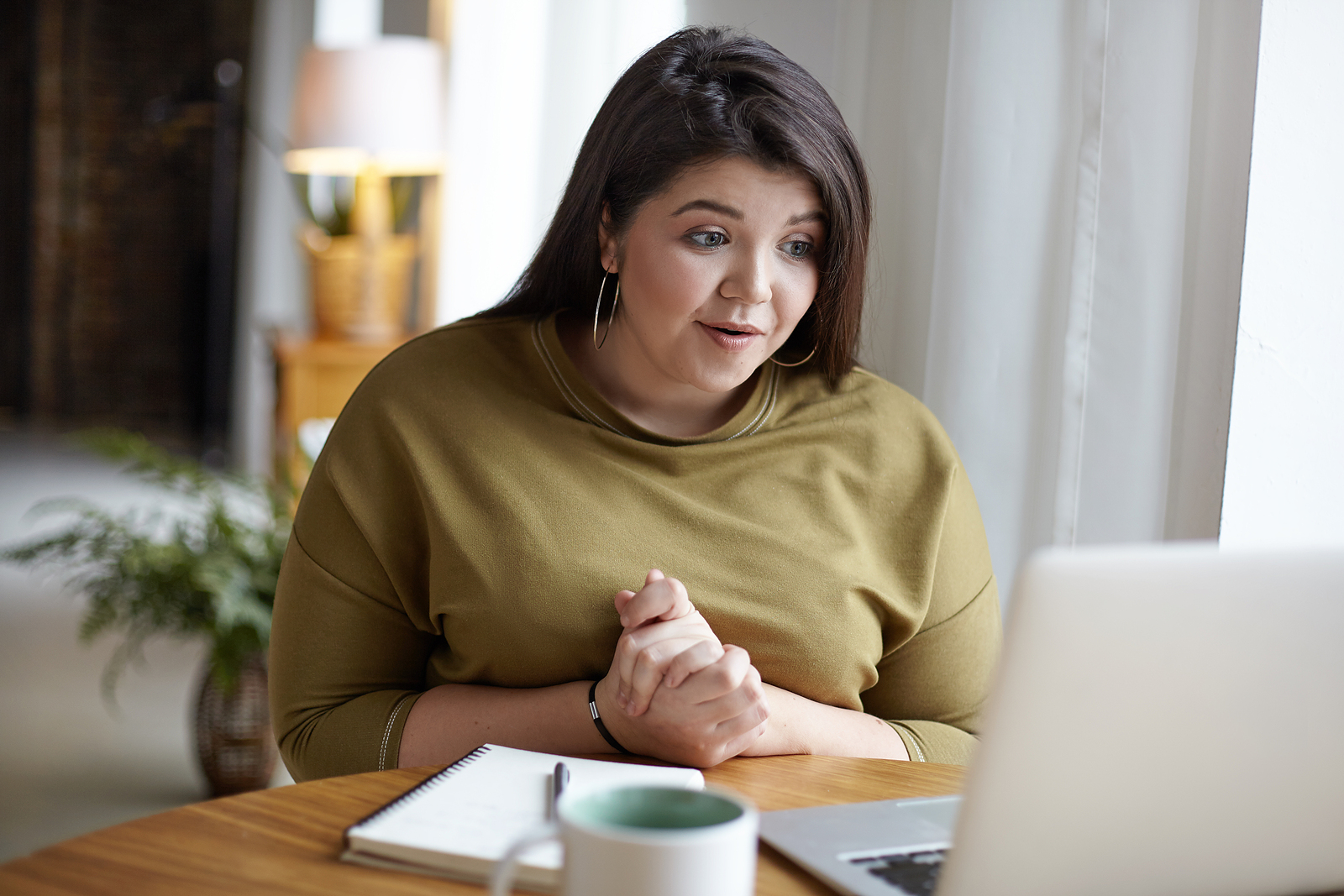 A woman smiles while using a laptop. She is feeling better after starting anxiety therapy in Birmingham, AL with Empower Counseling through online therapy in Auburn, AL.