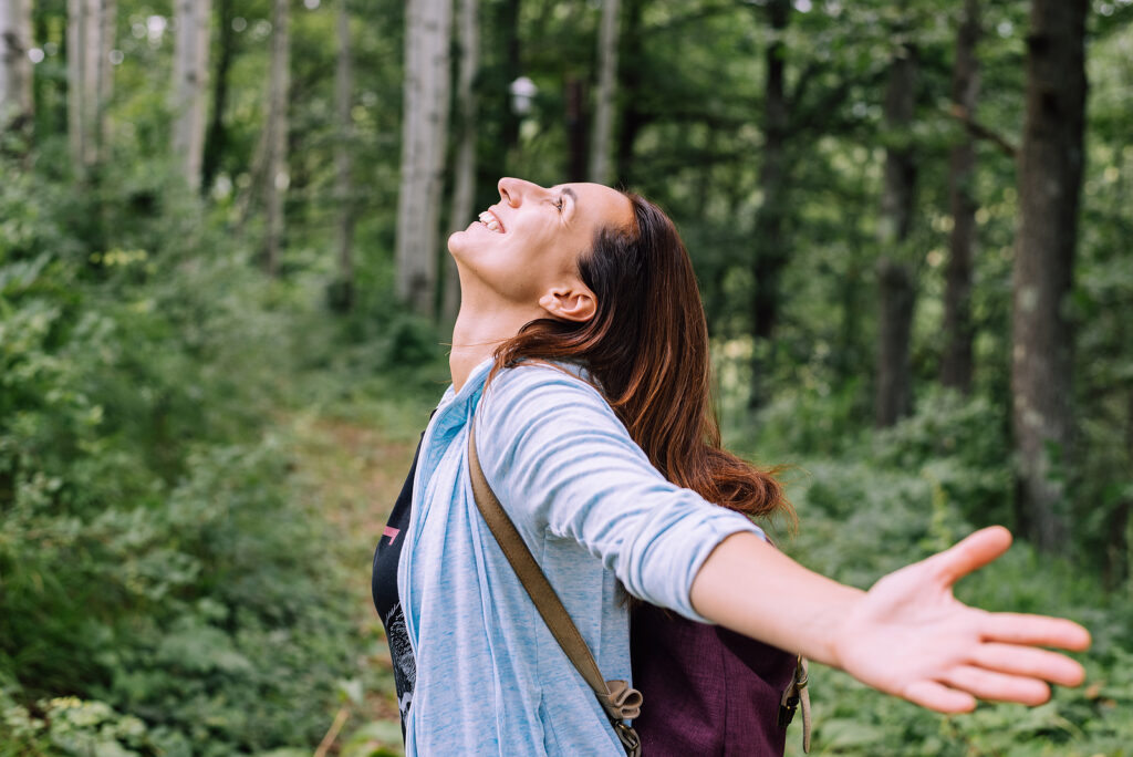 A girl is looking happy in the woods. She has started therapy for college students in Auburn, AL with Empower Counseling.