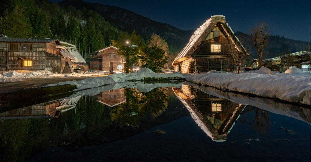 A pond and snow covered ground with a house, mountain and trees in background that Empower Counseling client is looking at practicing mindfulness