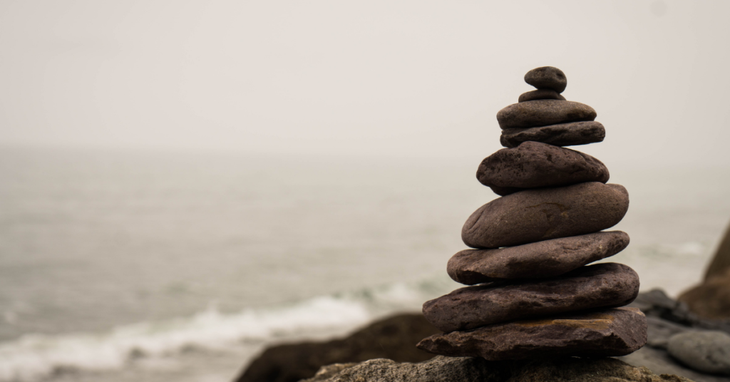 Rocks piled from large to small while person looking at them practices mindfulnesss for covid stress with Empower Counseling