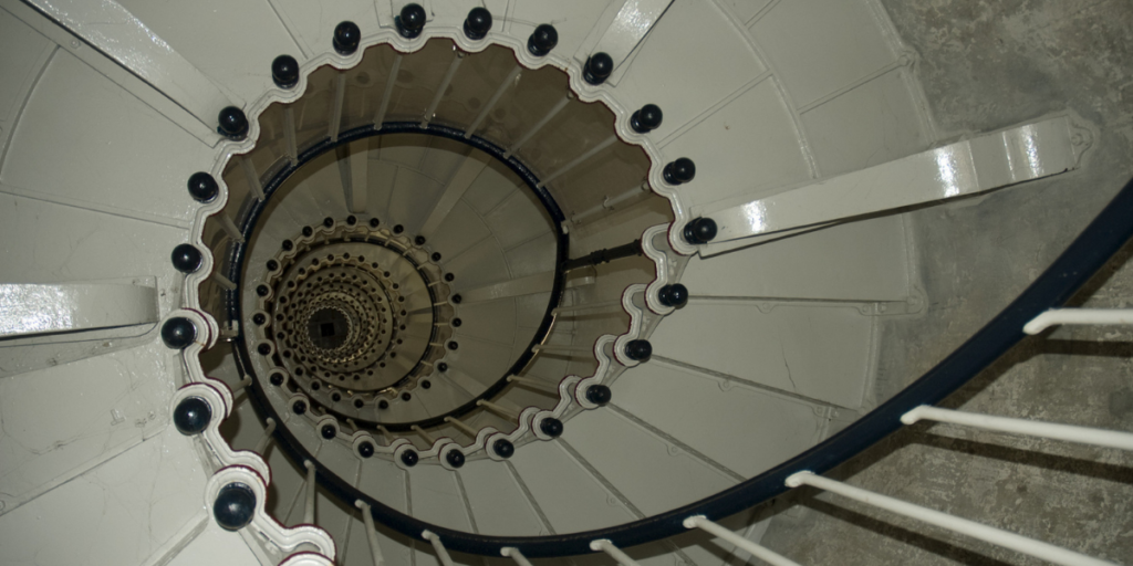 A never-ending spiral stair case looked at by someone in need of anxiety counseling for perfectionism by Empower Counseling in Birmingham Alabama