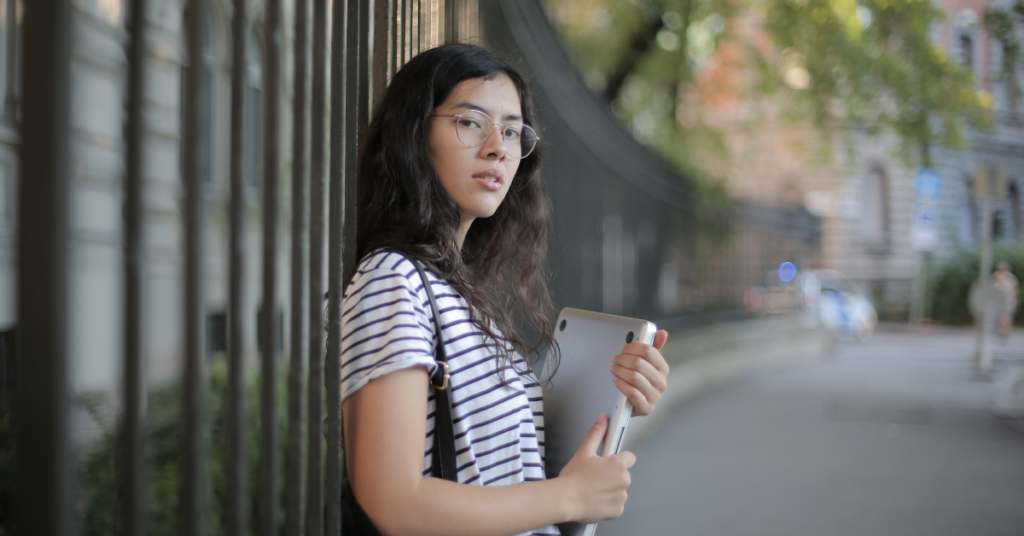 college female holding laptop and leaning against wall before anxiety counseling with Empower Counseling