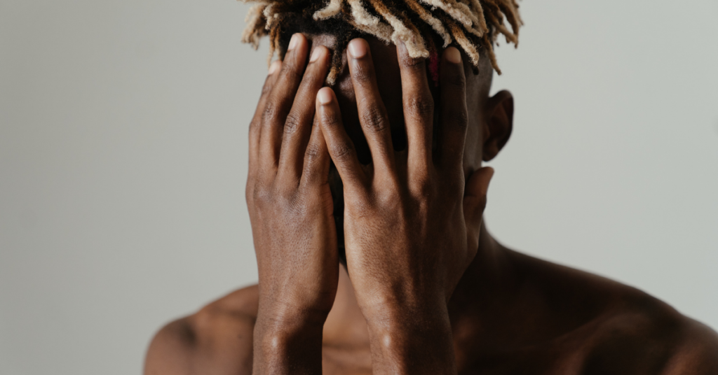 Depressed man with hands covering his face before depression counseling  with Empower Counseling in Birmingham Alabama