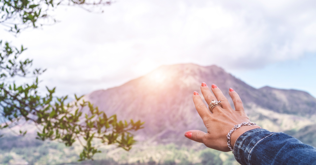 woman's hand reaching out to sunrise over a mountain after life coaching with Empower Counseling