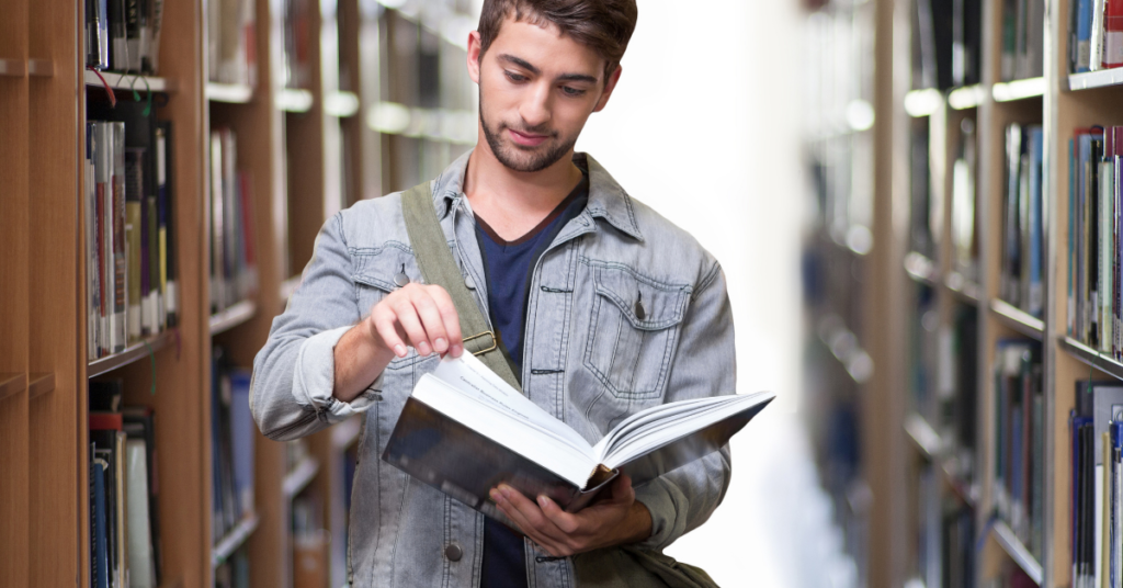 College male in library reading book before acceptance commitment therapy with Empower Counseling