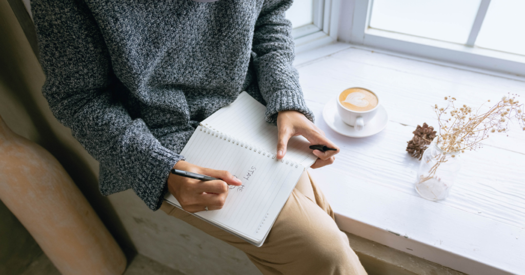 A women writing in journal after Acceptance Commitment Therapy with Empower Counseling
